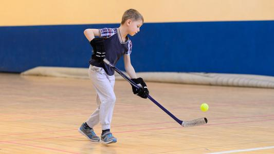 child playing floor hockey