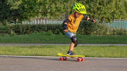 child wearing safety equipment practicing to skateboard