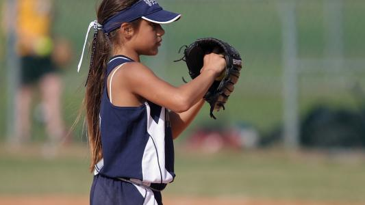 young girl in baseball uniform about to pitch