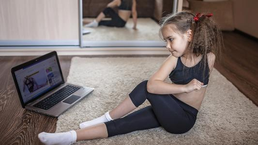 young girl in watching online video doing fitness exercises at home